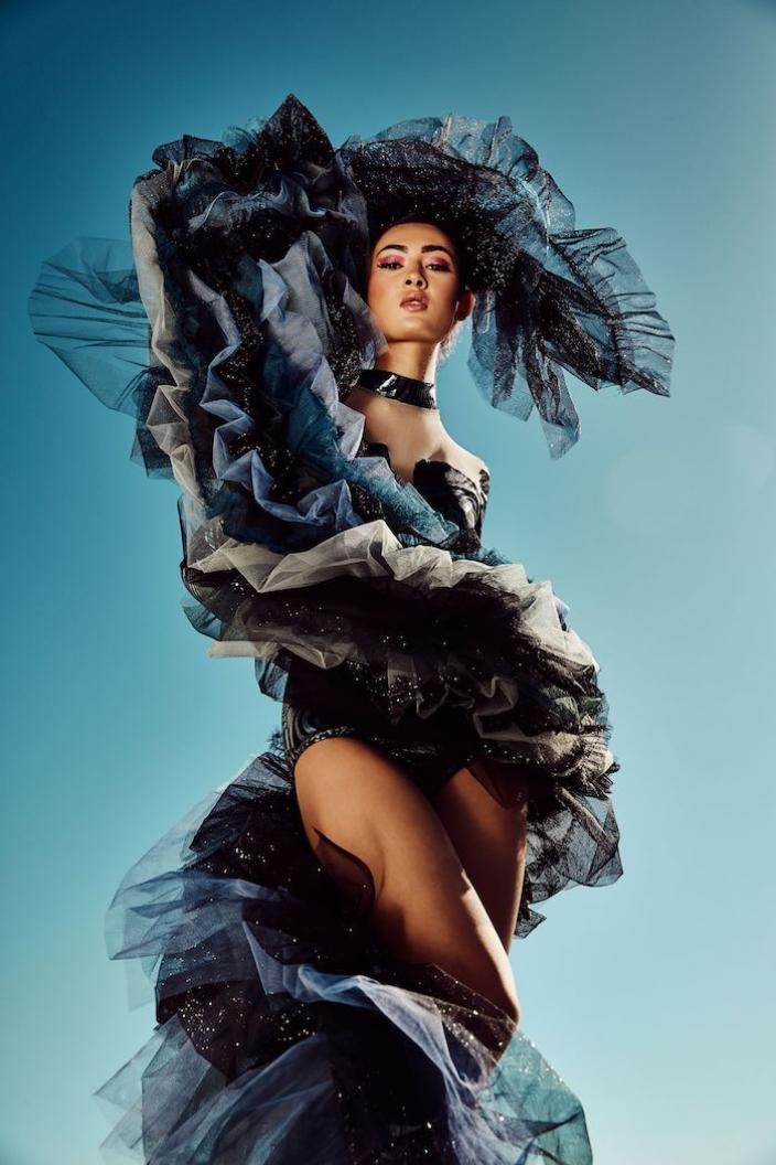 A model wrapped in a striking, sculptural ruffled furl of dark tulle