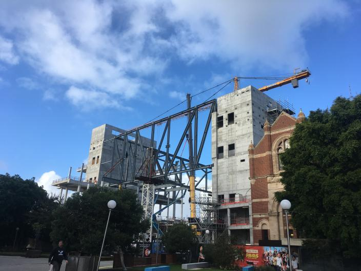 """""""Construction site showing large metal structural beams against a blue sky."""""""