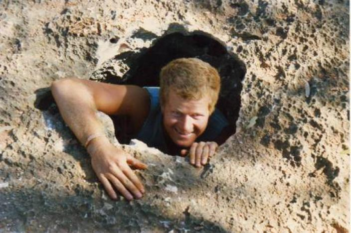 Photo of a man climbing out of a hole taken during a subterranean biology field trip.