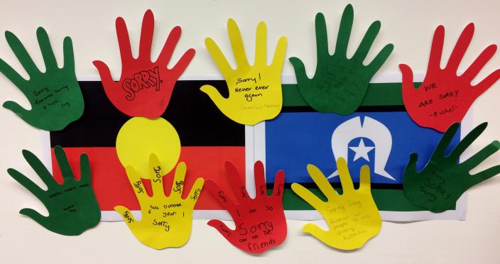 """10 hands are cut out from coloured paper with apologies written on them. They are stuck around Aboriginal and Torres Strait Islander flags."""