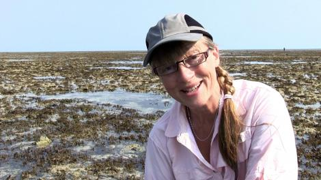 Sue Morrison crouched down on a reef talking to the camera