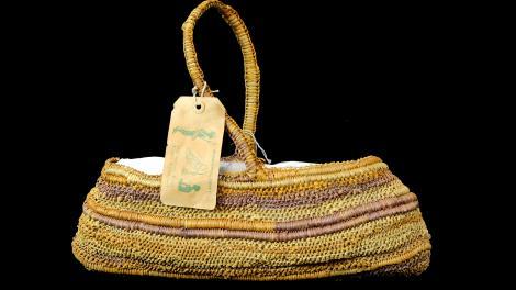 An open, oblong shaped, single handle basket.