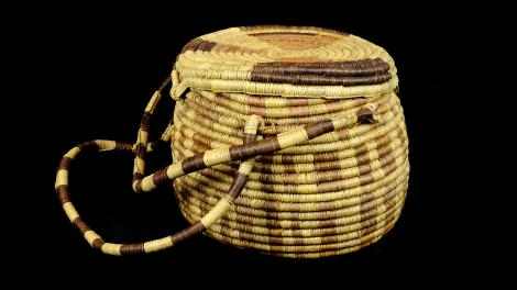 A large round lidded basket with a double handle and a woven latch.
