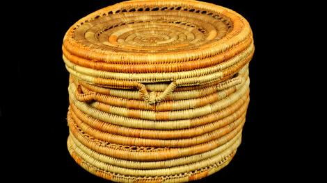 A round, yellow and orange, coiled basket with a lid but no handle.