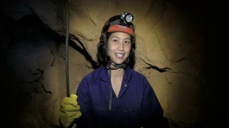 A lady descending into a cave