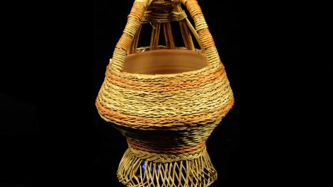 A natural and red/orange basket. It has a hollow base that angles upwards.