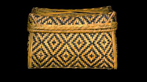 A lidded, rectangular, black and natural coloured basket  with a diamond design.