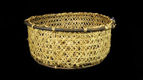 A straight sided and round basket made from split bamboo with a willow rim.