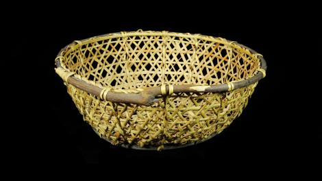 A round basket with sloping sides. It is made frosplit bamboo with a willow rim.