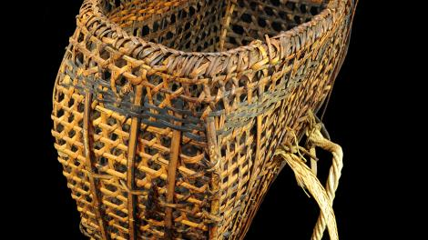 An open wickerwork basket made from split bamboo, rattan and rope straps.