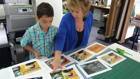 A child and adult looking through a series of advertisements