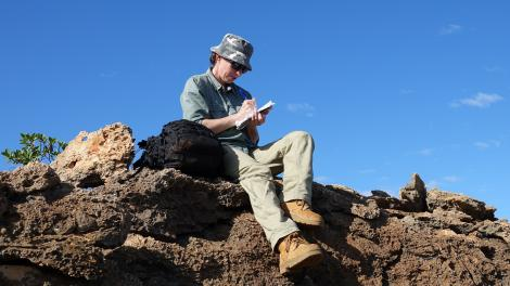 A person sitting on a rocky outcrop