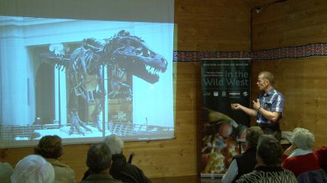 Mikael Siversson presenting a slideshow with a slide of a T-Rex fossil
