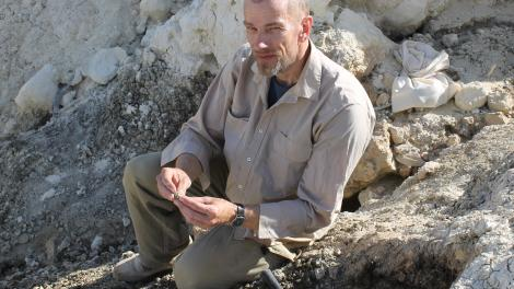 A person doing fieldwork holding an object