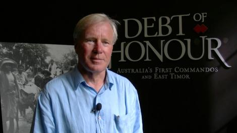 James Dexter standing in front of entry to the exhibition Debt of Honour