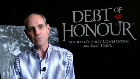 Stephen Anstey standing in front of entry to the exhibition Debt of Honour