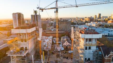 New Museum building site with crane in the middle, the sun is rising to the left side of the picture and the image has hues of blue and pink from the sunrise