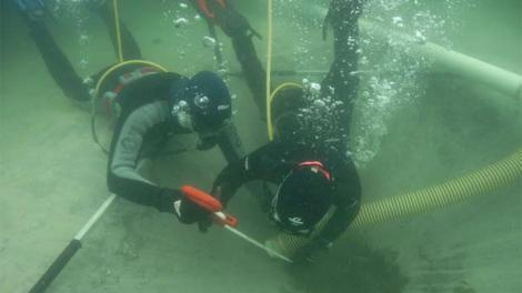Two divers excavating an underwater wreck location
