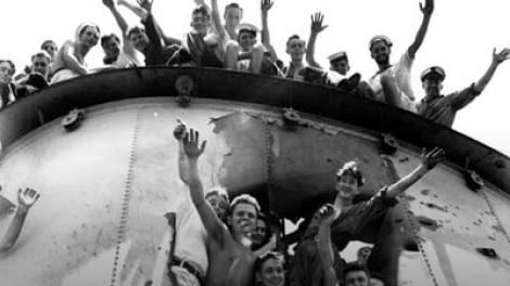 The crew of HMAS Sydney (II) posing through the damaged forward funnel