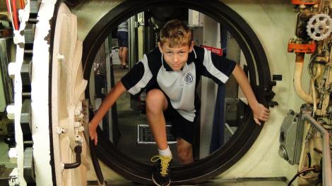 A school boy climbing through a circular submarine entry
