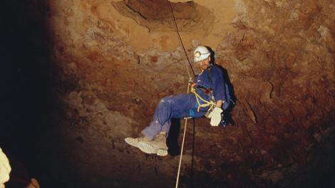 A scientist climbing down into an underground cave
