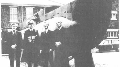Several people standing in front of a moored submarine