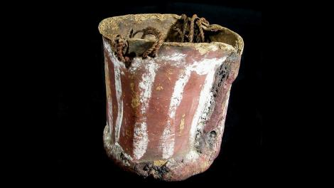 A bucket constructed out of bark and painted