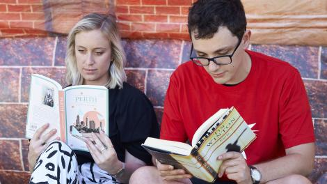 """""""A man and a woman reading Western Australian literature outside the Inflatable Museum."""""""