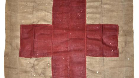 """""""100 year old flag with red cross symbol."""""""