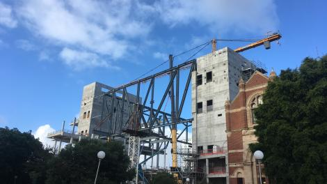 """Construction site showing large metal structural beams against a blue sky."""