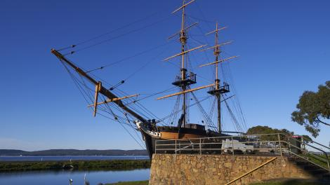 A Brig is moored near a stone wall beneath a clear blue sky