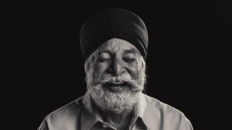 """""""Man with silver beard wearing turban laughs, his eyes are closed."""""""