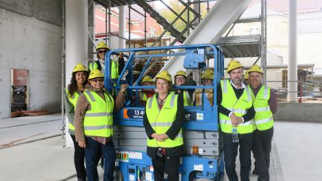 """""""People in yellow high visibility jackets stand around a blue scissor lift."""""""