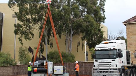 Two workers holding the straps around a large chiller.  The chiller is about to be craned onto the roof of the Art Gallery of WA