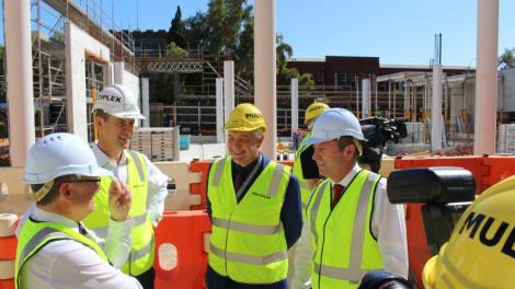 Four men in hard hats and hi-vis vests stand in discussion at the New Museum site.