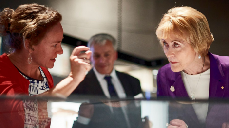 """""""A woman is carefully explaining a Museum object to another woman at an exhibition."""""""