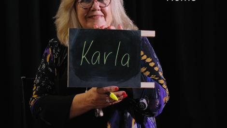 """A woman holds up a small chalkboard that reads 'Karla'. Text reads 'Home'."""