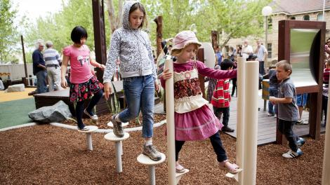 Children walking on stilt-like equipment in a play space