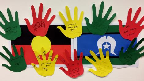 """""""10 hands are cut out from coloured paper with apologies written on them. They are stuck around Aboriginal and Torres Strait Islander flags."""""""