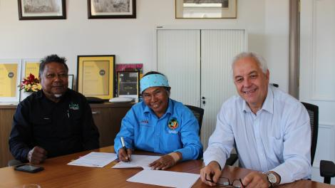 """""""Three people at a boardroom table smile for the camera while one signs a document."""""""