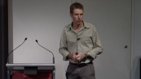 Glenn Moore stands at a podium, presenting a lecture
