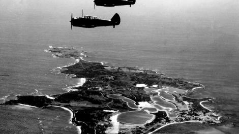 Black and white image of planes flying over an island