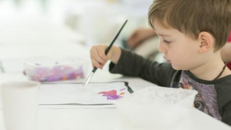 Child painting a collage in the Museum of Us