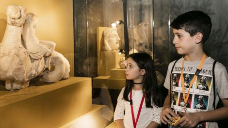 """Two children look at an artefact from the exhibition with great curiosity."""