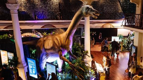 """""""A large crowd of people drinking and standing around an animatronic dinosaur."""""""