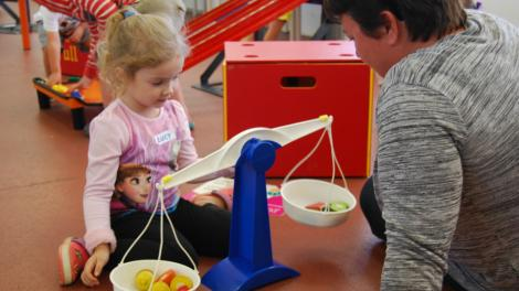 """""""A child and guardian are experimenting with different weights on a scale."""""""