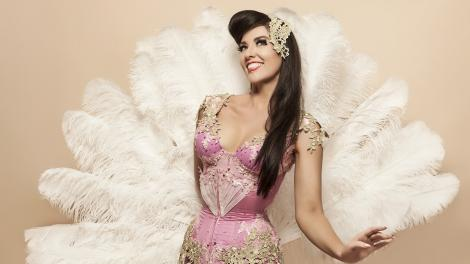 """A burlesque dancer wearing a pink silk outfit, surrounded by white feathers."""