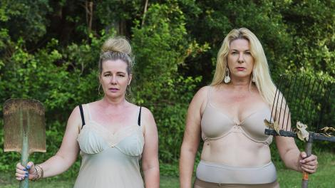 """Two women are standing in their underwear holding garden tools."""