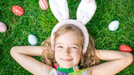 """A young girl with bunny ears on, lying down surrounded by Easter eggs."""