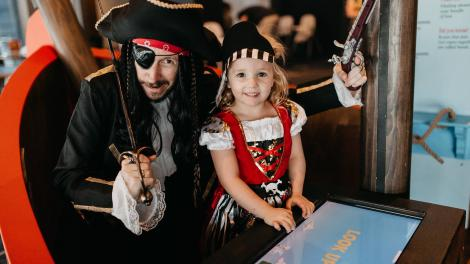 """""""A man and a small girl both dressed as pirates, posing for a photo."""""""